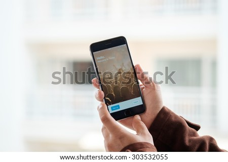A man trying to log in Twitter application using Apple iPhone 6. Twitter is largest and most popular social networking site in the world.CHIANG MAI, THAILAND - AUG 06, 2015 - stock photo