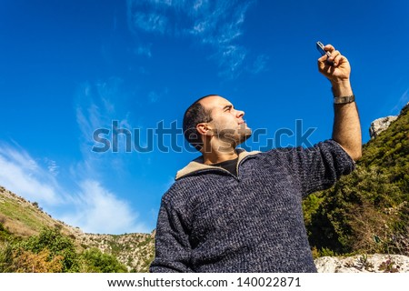 a man trying to pick up the signal on his mobile phone - stock photo