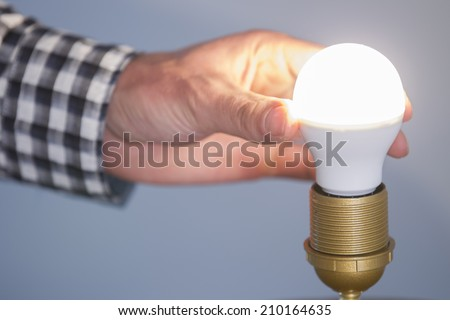 A man turning a lighted fluorescent lightbulb in his own house - stock photo