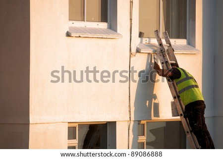 A man up a ladder painting the exterior of a house - stock photo