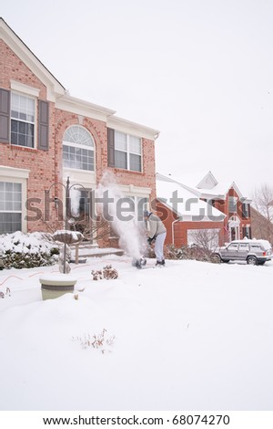 A man uses a snow blower to clear the freshly fallen snow off the sidewalk in front of his house in winter.