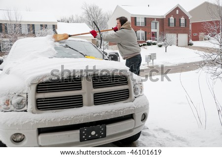 A man using a broom to sweep snow off the windshield of his truck after a winter storm. - stock photo