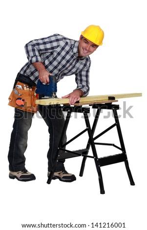 A man using a jigsaw - stock photo