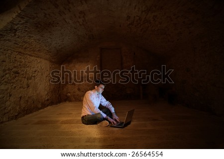 a man using a laptop in a cellar