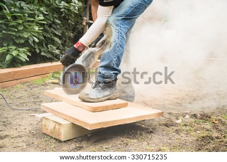 A man using a rotary cut-off concrete saw to cut patio slabs to size. Dust from the rotating saw can be seen. - stock photo