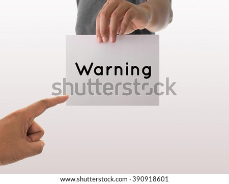 a man using hand holding the white paper with text warning