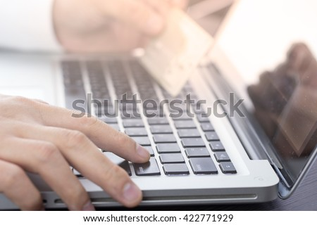 a man using his computer laptop and holding credit card intent to shopping online concept,  digital business or e-commerce. warm tone. - stock photo