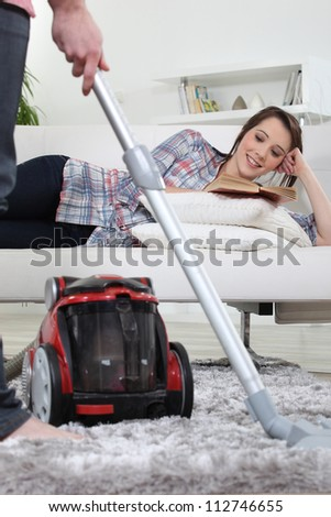 A man vacuuming while his girlfriend is reading a book.