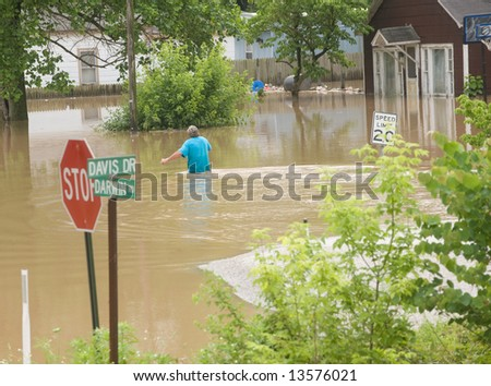 A man wades through flood water in rural Indiana