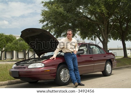 A man waiting for a tow truck or assistance of some sort. - stock photo