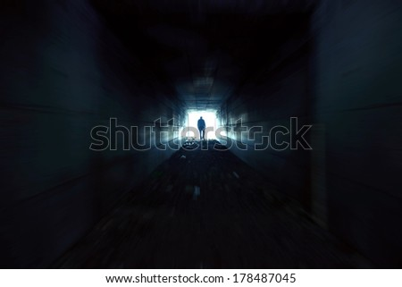 A man walking alone in the dark tunnel - stock photo