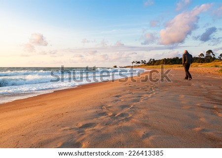 A man walking along Baltic sea shore at sunset light on stormy weather - stock photo