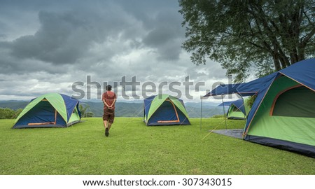 A man walking around camping site