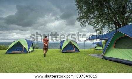 A man walking around camping site - stock photo