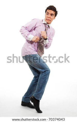 A man walking by stealth with grimace on his face, wearing jeans, shirt and tie, isolated on white - stock photo