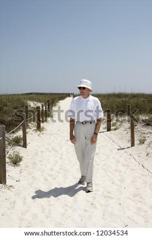 A man walking down a path to the beach. - stock photo