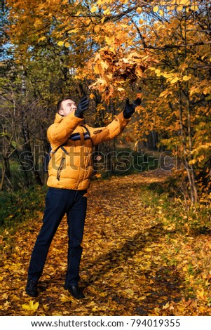 A man walking in the autumn forest plays with fallen leaves. The nature reserve of the valley of the river Skhodnya. Kurkino. Moscow. Russia.
