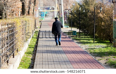 a man walking in the path of the sidewalk