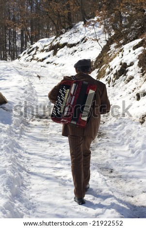 a man walking in the snow carrying his accordion - stock photo