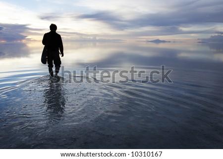 a man walking in to heaven in a uyuni salt lake bolivia - stock photo