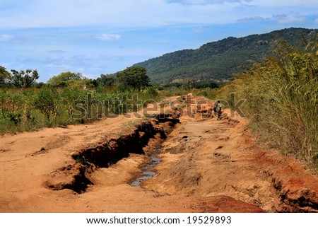 a man walking on a road to nowhere in Africa - stock photo