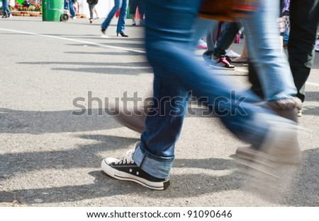 A man walking on concrete with work boots on. - stock photo