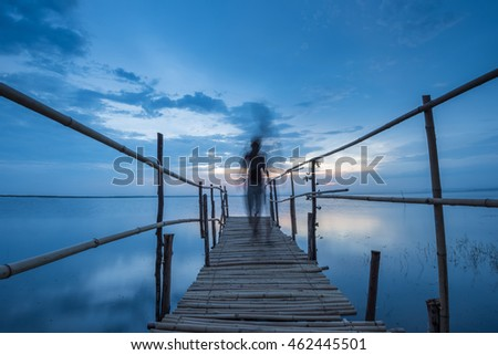 A man walking on the bamboo bridge at lake