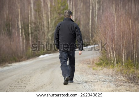 A man walking on the road. Image taken in a spring time. - stock photo