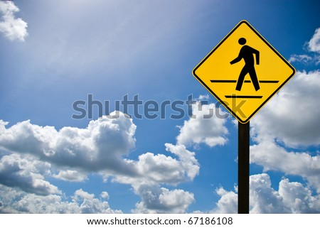 A man walking sign with cloudy sky