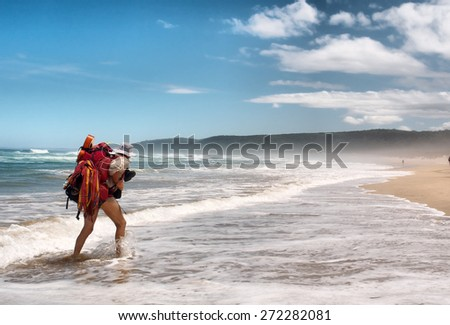 A man walks on sea beach. Shot on the Otter trail in the Tsitsikamma National Park, Garden Route area, Western Cape, South Africa.  - stock photo
