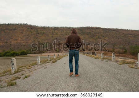 a man walks on the road with mountain