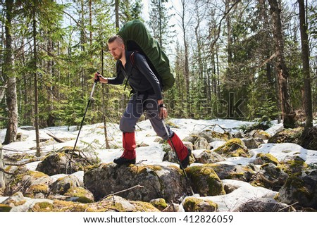 A man walks over rocks in the woods