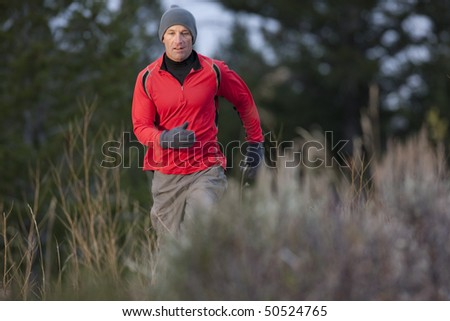 A man walks toward the camera through a brush-filled clearing. He is looking downward and wearing a hat, gloves, and activewear. Horizontal format. - stock photo