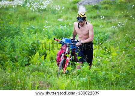a man walks with his bicycle in the park to park for recreation. - stock photo