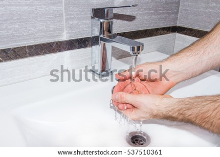 A man washes his hands in the bathroom. Background white ceramic bathroom faucet.