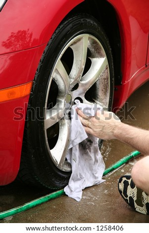 A man washing a wheel of a car.  There is slight motion blur on the hand as it washes. - stock photo