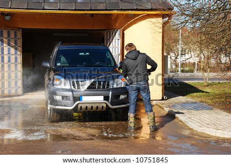 A man washing his car - stock photo