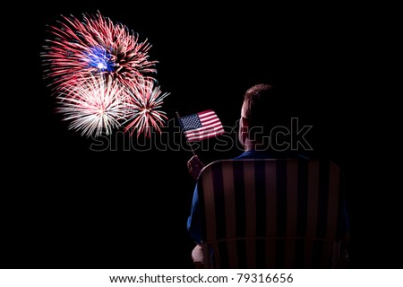 A man watches a fireworks show while waving an American flag.