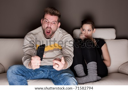 A man watching a game, while his girlfriend is sitting besides him bored. Showing the differences between the sexes. - stock photo