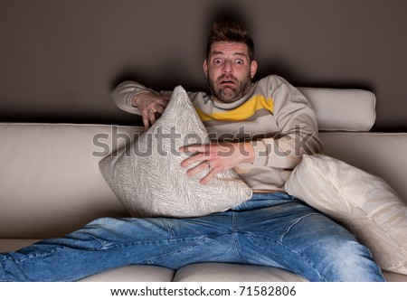 A man watching a horror movie. On the couch. - stock photo