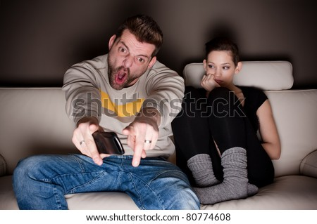 A man watching football, while his girlfriend is sitting besides him bored. Showing the differences between the sexes. - stock photo