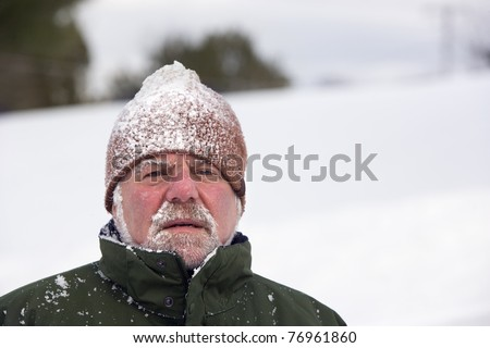 A man wearing a beanie cap and covered with snow is looking at the camera with an unhappy expression. Horizontal shot. - stock photo