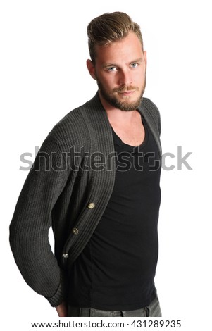 A man wearing a black shirt and grey sweater standing against a white background, smiling to camera. - stock photo