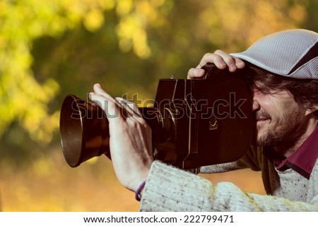 A man wearing a cap with an old movie camera. Shooting reportage in autumn - stock photo