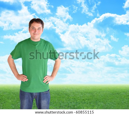 A man wearing a green t-shirt is smiling and standing in front of bright blue clouds and green nature grass. Use it for a recycling, peace or happiness concept. - stock photo