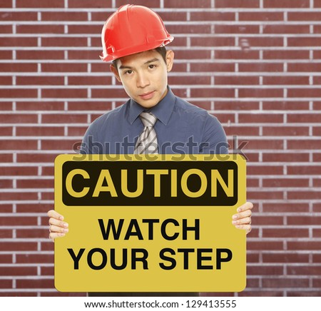 A man wearing a hardhat and holding a caution sign - stock photo