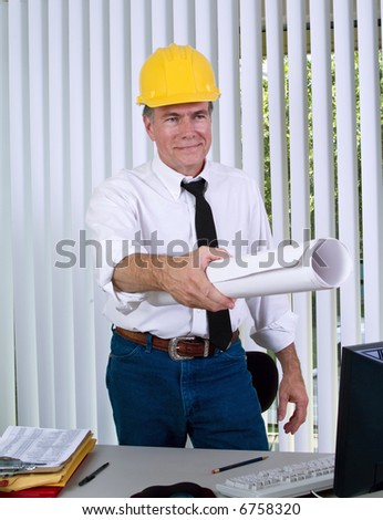 A man wearing a hardhat giving what appears to be drawings to someone - stock photo
