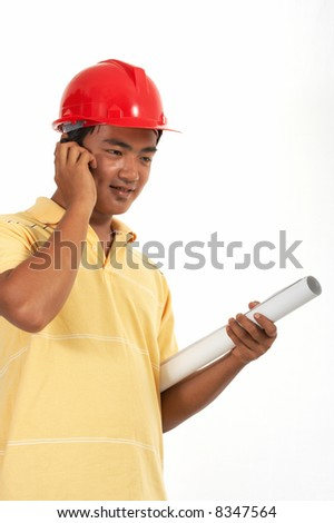 a man wearing a hardhat while talking on the phone - stock photo