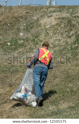 A man wearing a reflective vest, picking up spring garbage