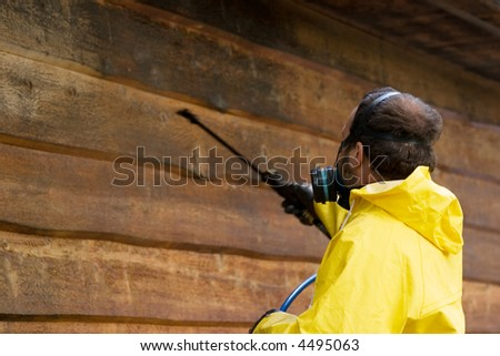 a man wearing a respiratore while he sprays some siding - stock photo